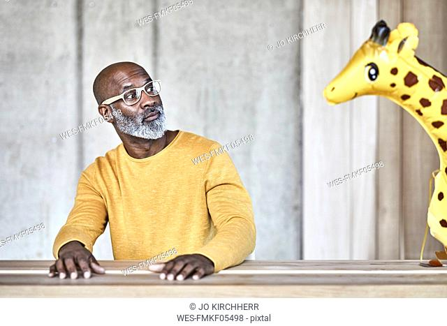 Surprised mature businessman sitting at desk in office looking at giraffe figurine
