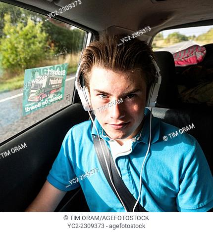 A 14 year old boy listening to music in the car