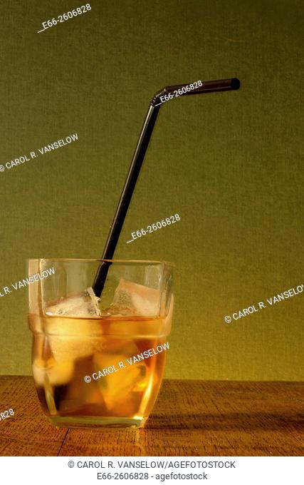 Shot of whiskey on the rocks with black bending straw. Concept: under age drinking