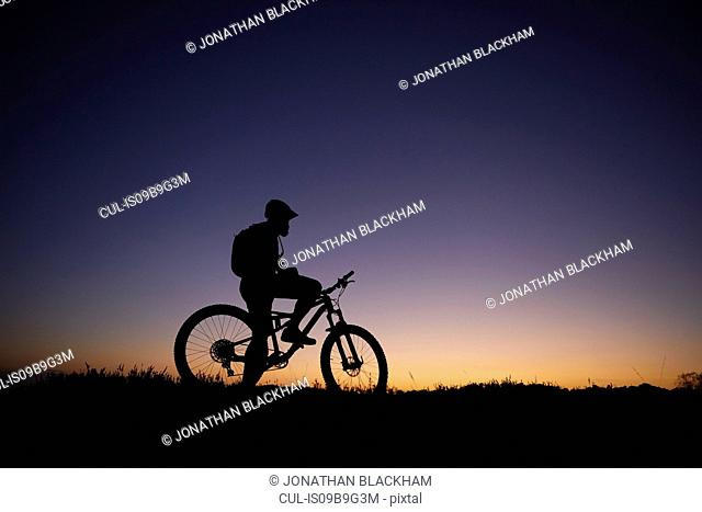 Silhouetted male mountain biker looking out at sunset