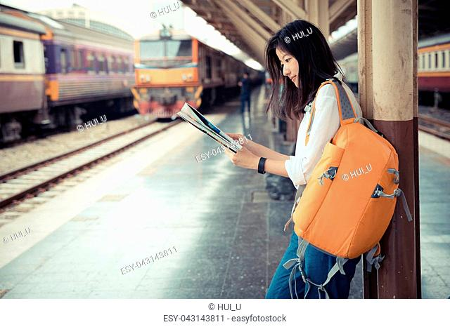 tourist searching route on map at train station, travel concept