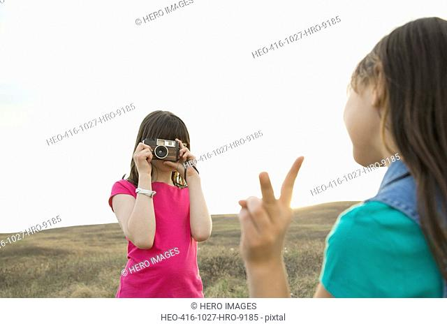 Girl photographing female friend during field trip
