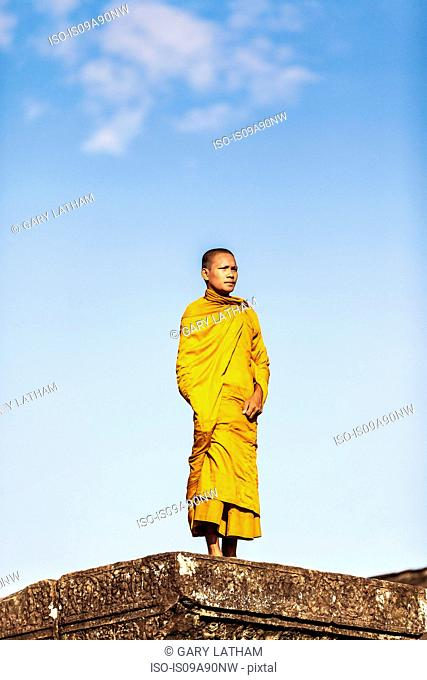 Young Buddhist monk standing outside temple in Angkor Wat, Siem Reap, Cambodia
