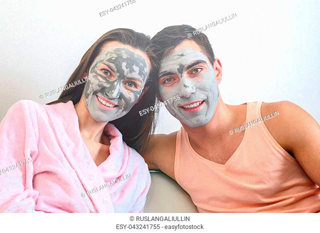 Emotional portrait of a married couple in masks made of clay. day Spa, Wellness, skincare