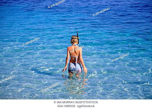 Young girl snorkelling blue clear sea water, Sicily, Italy