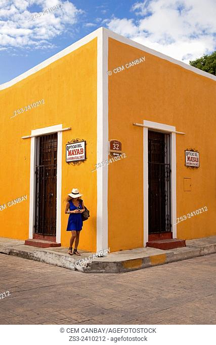 Woman in front of a colonial house, Izamal, Yucatan Province, Mexico, Central America