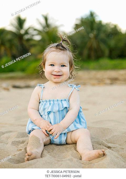 Baby girl wearing blue dress sitting on beach