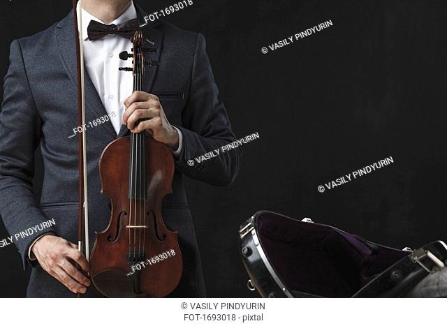Midsection of man holding violin while standing by case against black background