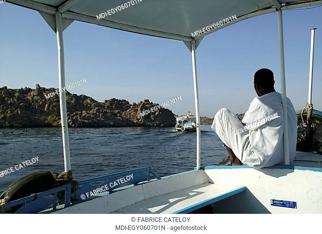 Egyptian sitting at the front of a motorboat going to the Philae Temple