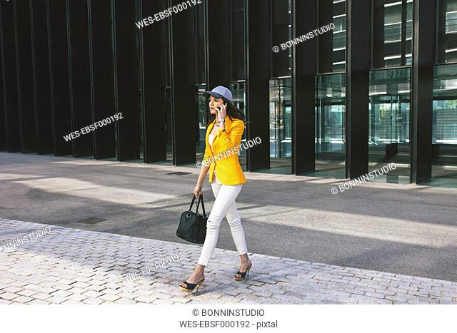 Spain,Catalunya, Barcelona, young modern woman with yellow jacket on the move
