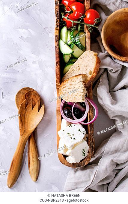 Ingredients for traditional greek salad. Cherry tomatoes, cucumbers, onion, black olives, feta cheese in olive wood bowl with loaf bread