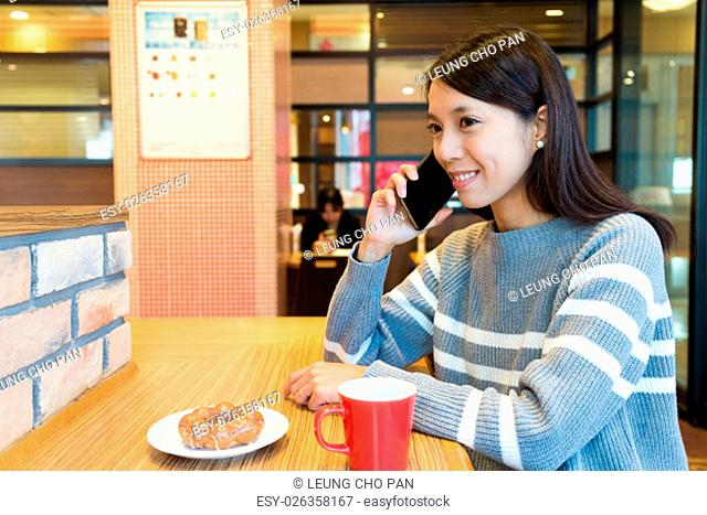 Woman talk to cellphone and enjoy her breakfast in coffee shop