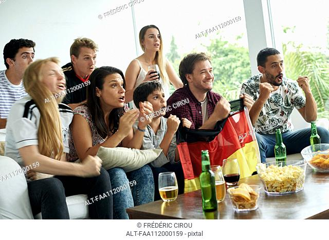 German football fans watching football match at home