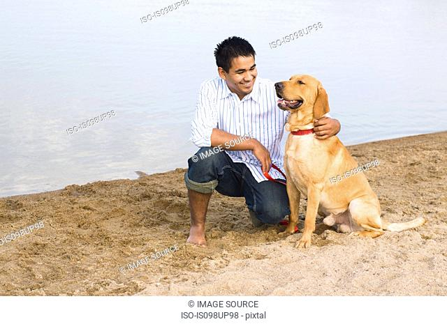 Man and golden retriever at the beach