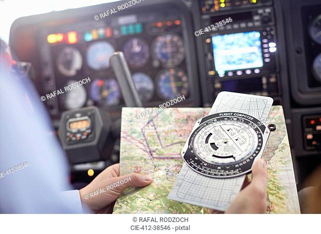 Pilot checking navigational map and compass instrument in airplane cockpit