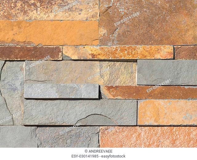 wall made of natural decorative stone with a rough gray and brown textured surface similar to rust