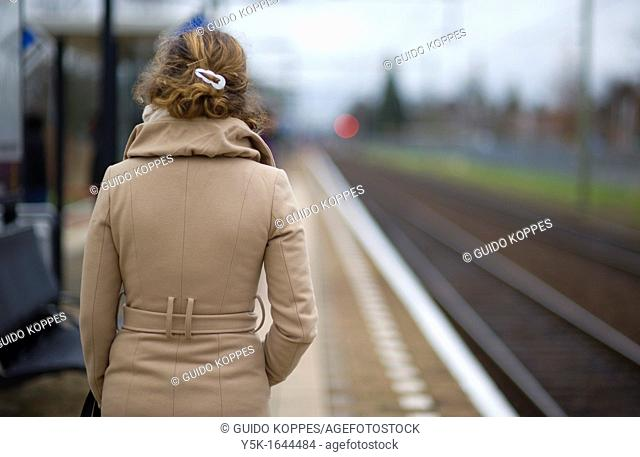 Oisterwijk, Netherlands. Young woman in waiting for her commuter-train from Oisterwijk to Tilburg, Netherlands on the platform of this small railway-station