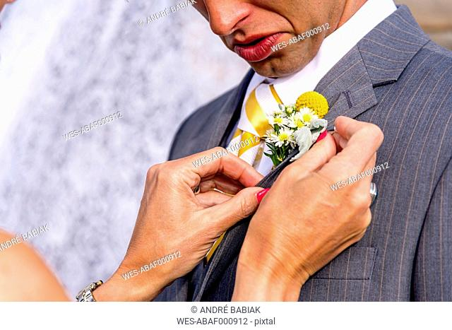USA, Texas, Future mother in law adjusting boutonniere at grooms suit