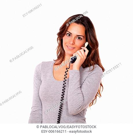 Portrait of a stylish young female talking on phone while standing in white background