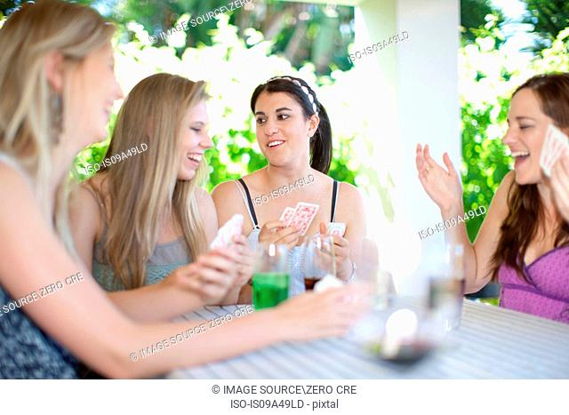 Women playing cards at table