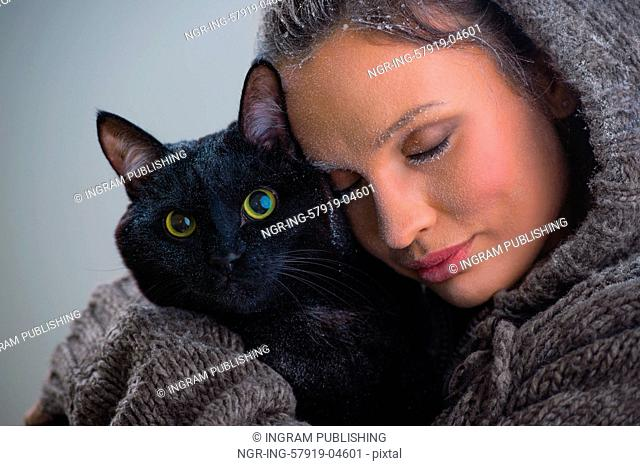 Winter portrait of young kind woman holding big black cat. Frost and snow on them