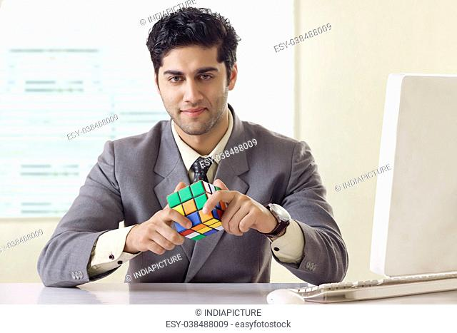 Businessman solving Rubik's Cube puzzle