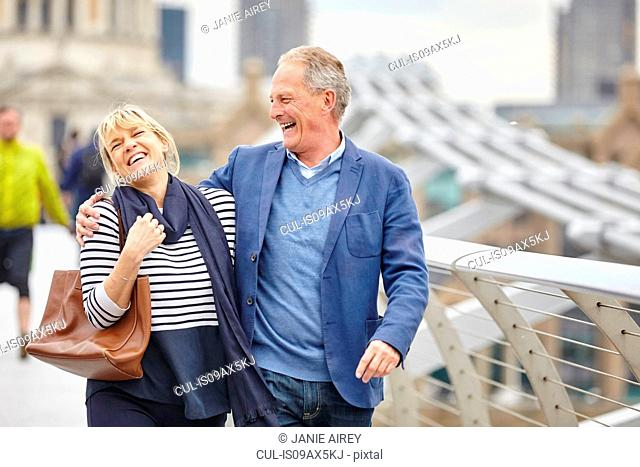 Mature dating couple laughing whilst crossing Millennium Bridge, London, UK