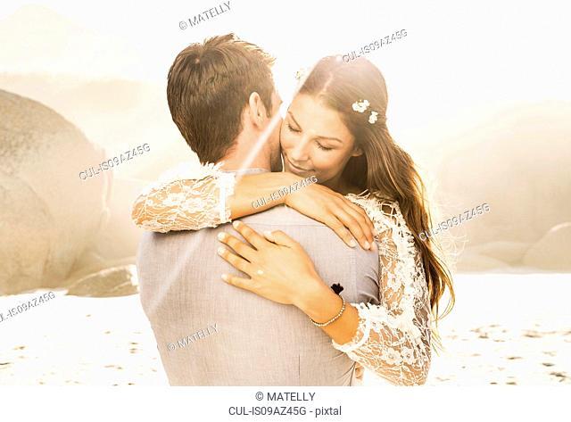 Woman hugging boyfriend on sunlit beach, Cape Town, South Africa