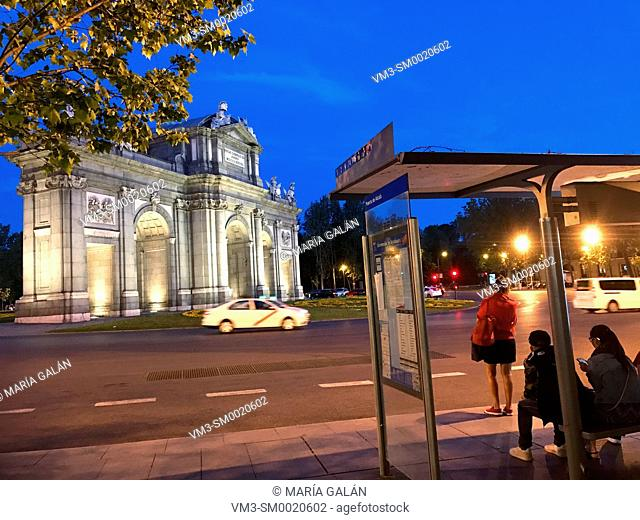 Bus stop and Alcala Gate, night view. Independencia Square, Madrid, Spain