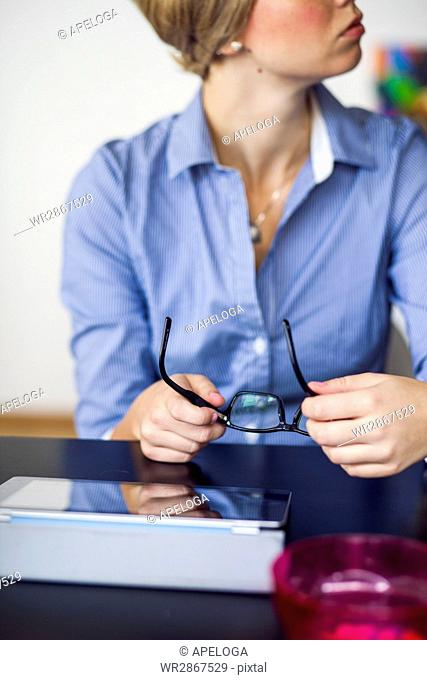 Midsection of creative businesswoman holding eyeglasses at desk