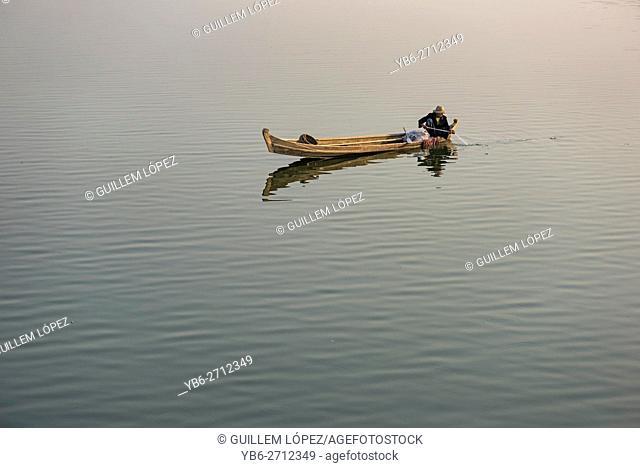 A local fisherman in his boat at the Taungthaman Lake, Amarapura, Myanmar