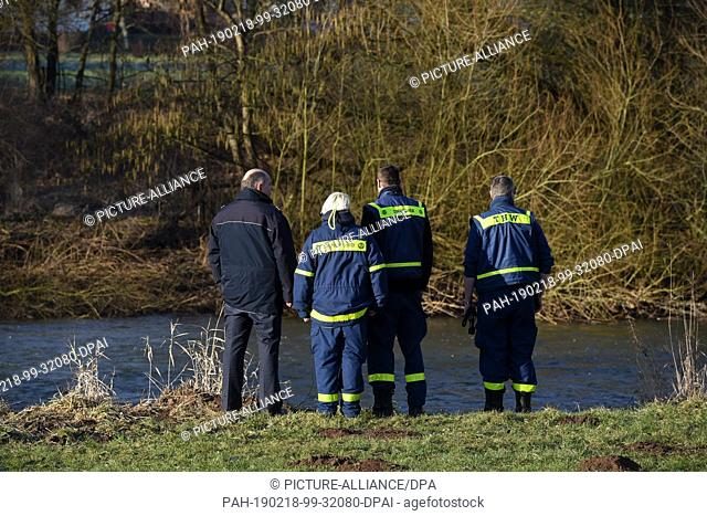 18 February 2019, Hessen, Guxhagen: THW rescue workers and a member of the water police search the banks of the Fulda River