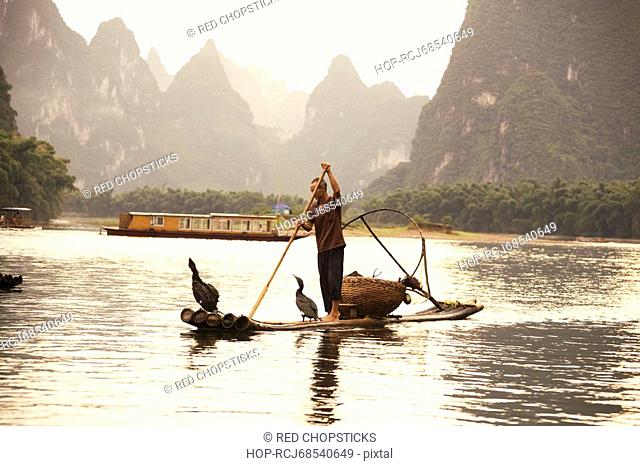 Fisherman on a wooden raft with a hill range in the background, Guilin Hills, XingPing, Yangshuo, Guangxi Province, China