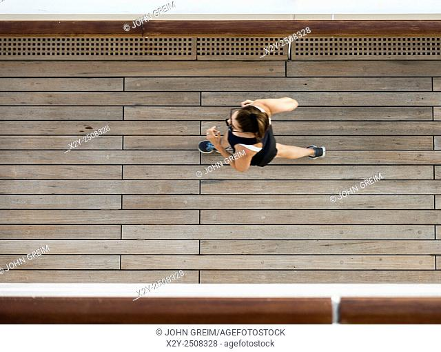 Woman jogging on the deck of a cruise ship