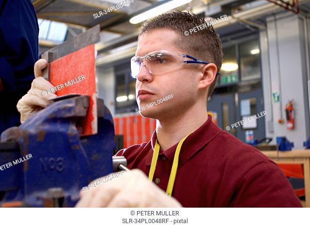 Worker measuring plastic in factory