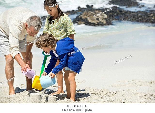 Children playing with their grandfather on the beach