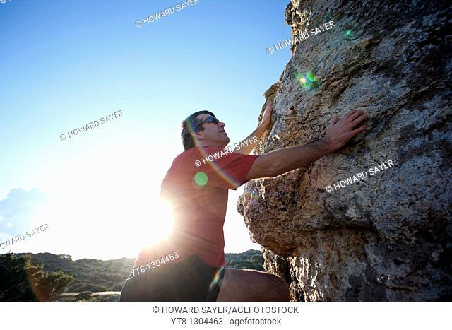 Man climbing up over rocks