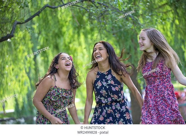 Happy Hispanic mother and two teen daughters having fun in the park