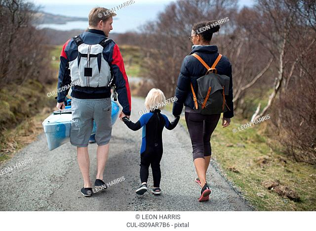 Family walking on country road holding hands, rear view