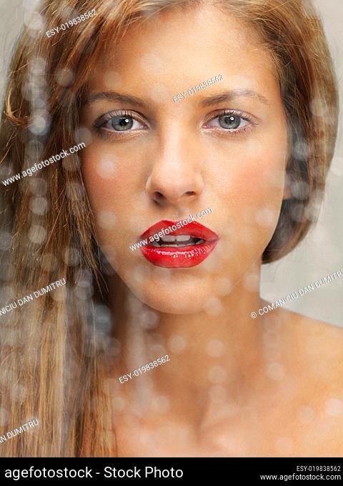 beauty portrait of woman behind wet window
