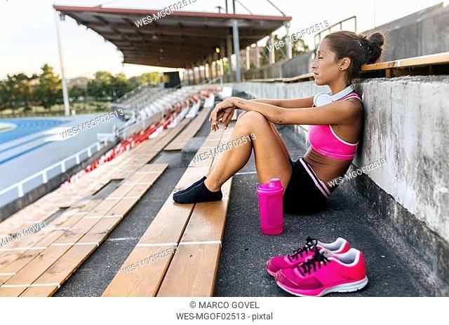 Female athlete taking a break, sitting in stadium