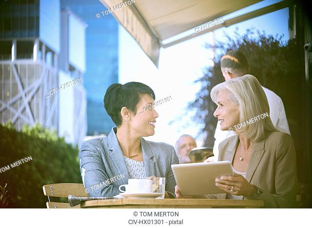 Businesswomen using digital tablet at urban sidewalk cafe