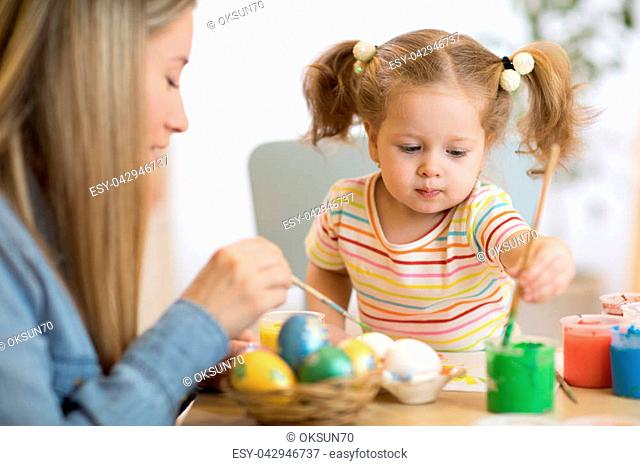 Mother and child painting on Easter eggs