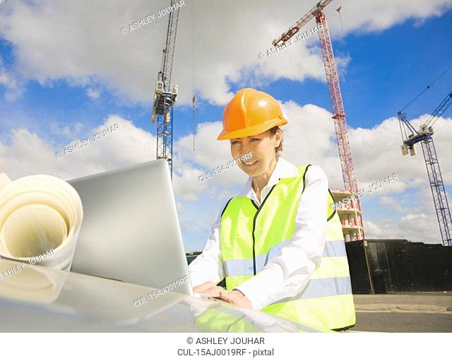 Woman looking at Laptop by Building Site