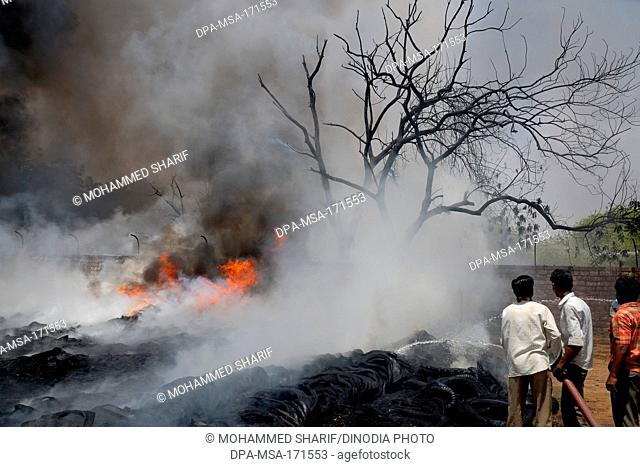 Firemen trying to douse off fire while scrap warehouse , Jodhpur , Rajasthan , India