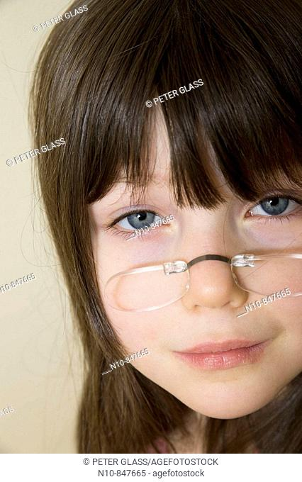 Young girl wearing glasses that attach directly to her nose
