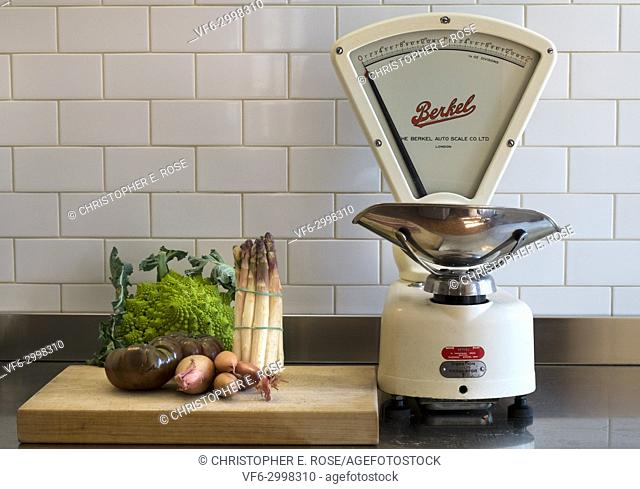 A few choice vegetables wait on a chopping board on a stainless steel kitchen work surface alongside a set of classic vintage grocers weighing scales made by...