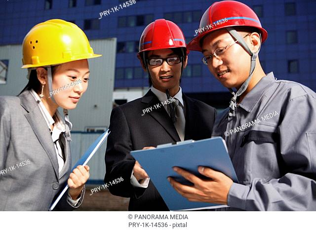 People in safety helmets standing together, talking about work