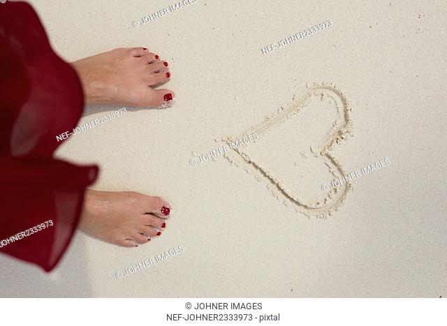 Feet in front of heart on sand