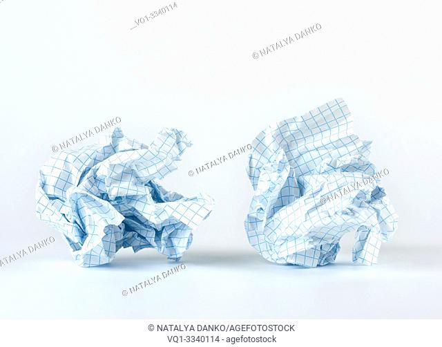 crumpled blank white sheet of paper into the cell from a school notebook, white background